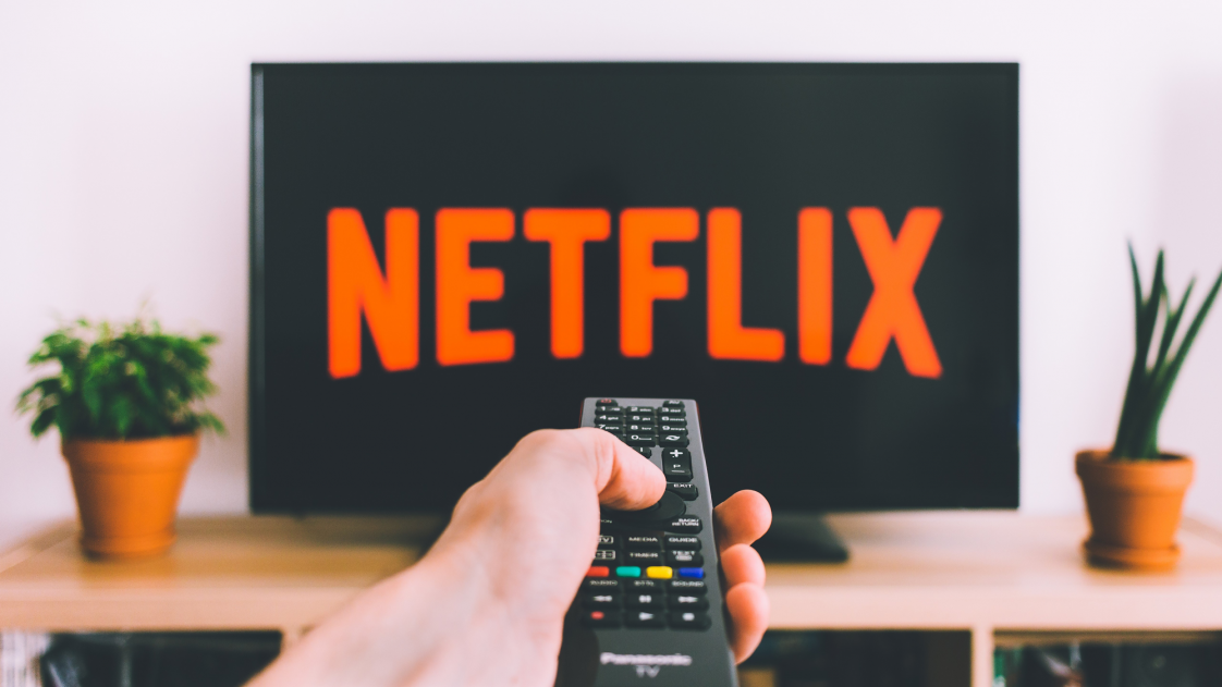 Image of person pointing remote at Netflix on television.
