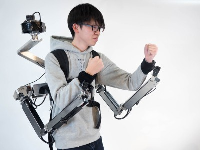 Image of man in a boxing stance wearing robotic-armed backpack.