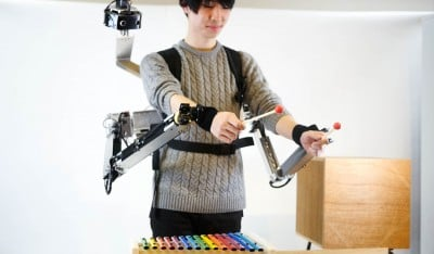 Image of man playing the xylophone wearing robotic-armed backpack.