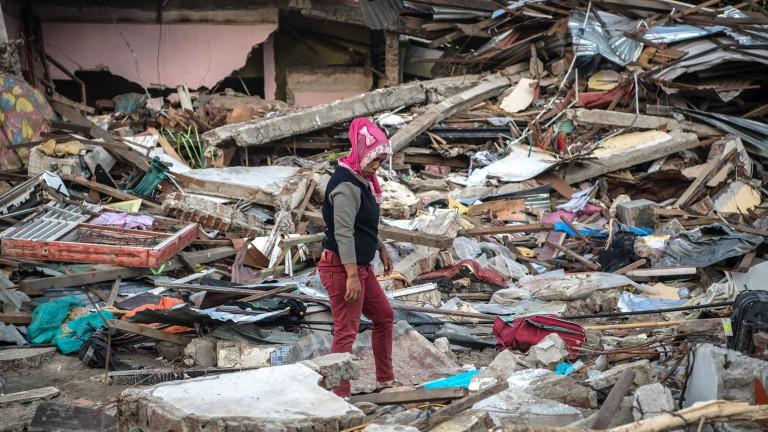 Photo of woman walking among tsunami/earthquake devastation