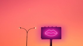 image of lips on billboard next to street light with sunset in background sex tech ces vibrator