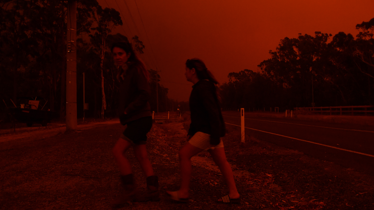 Photo of residents as they watch the developing conditions near the town of Sussex Inlet on December 31, 2019 in Sydney, Australia.
