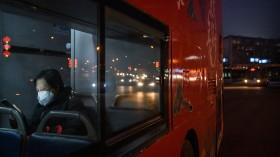 Beijing woman riding bus using mobile phone