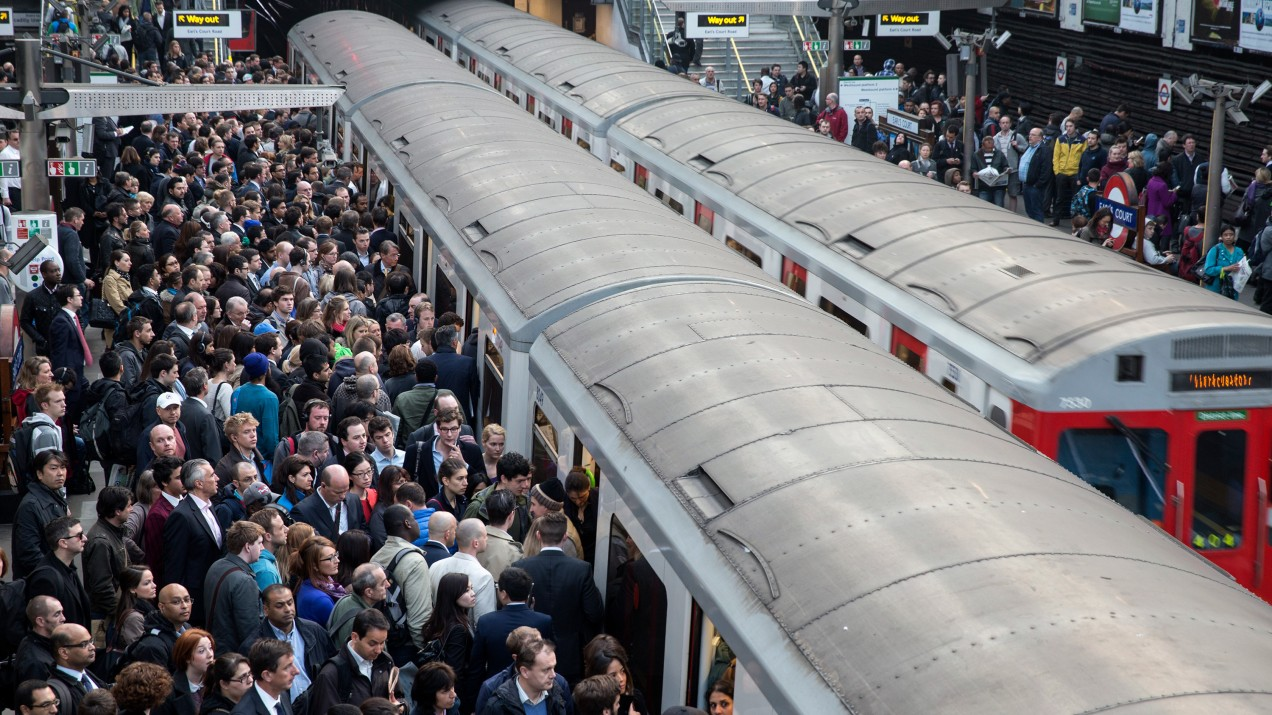 An image of people crowding onto train cars.