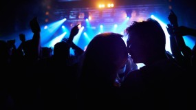 An image of people stealing a kiss in a crowd.