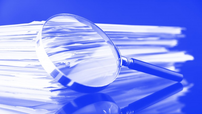 A stack of papers with a magnifying glass