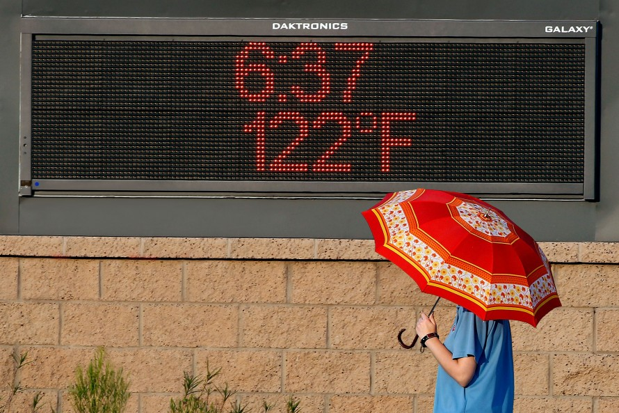 "Photo of person holding an umbrella in front of a screen showing the time ""6:37"" and temperature ""122 degrees F"""