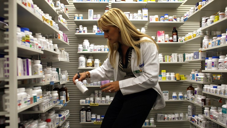 A pharmacist selects a bottle of medication from shelves and shelves of options.