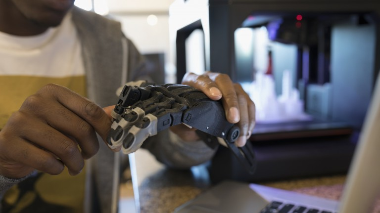 An image of a developer holding a robotic hand