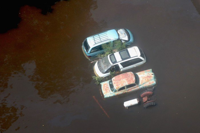 Photo of three cars and a tractor in flood waters