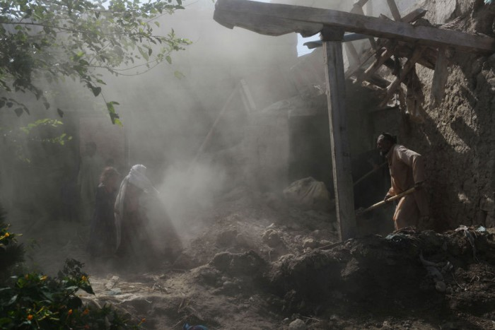 Afghan residents clear rubble from their homes.