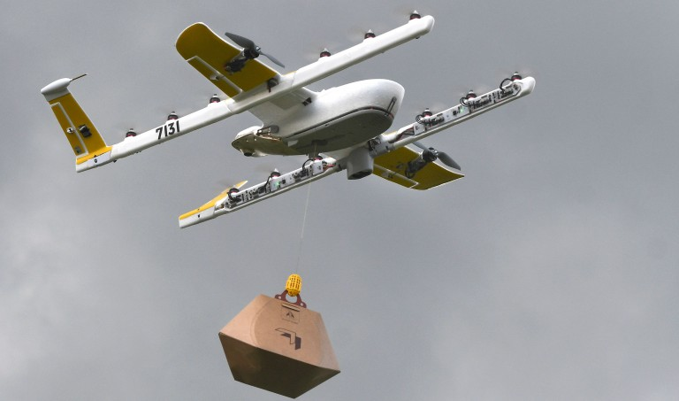 A Wing drone flying with a package in tow