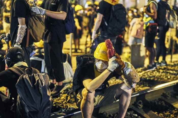Protestors resting and waiting to decide what the next move will be at the West Rail Station in Yuen Long.  The protestors are protesting the suspected collusion with Triads from last weeks Yuen Long West Rail station attacks on protestors and civilians.  Yuen Long, New Territories, Hong Kong. July 27th, 2019.