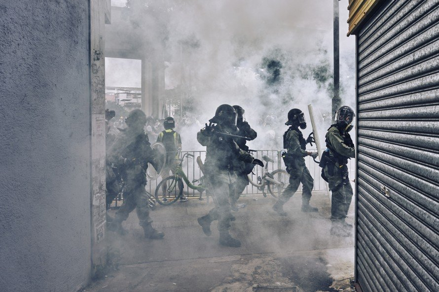 Riot Police begin shooting tear gas and  wielding their batons at protestors during a skirmish in Yuen Long.  The protestors are protesting the suspected collusion with Triads from last weeks Yuen Long West Rail station attacks on protestors and civilians.  Yuen Long, New Territories, Hong Kong. July 27th, 2019.
