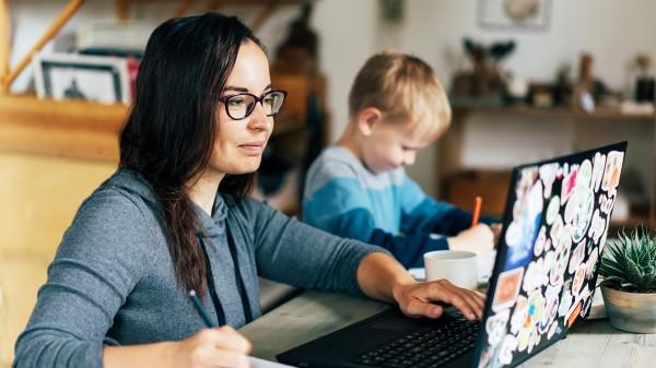 woman mom writing list down on paper with child next to her and computer asana trello jira google doc how to homeschool coronavirus