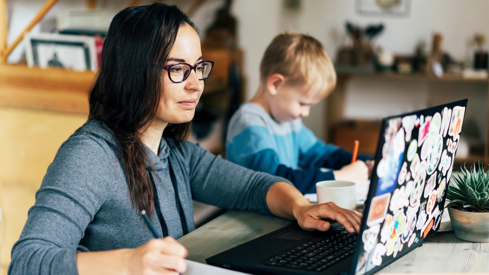 woman mom writing list down on paper with child next to her and computer asana trello jira google doc how to homeschool coronavirus