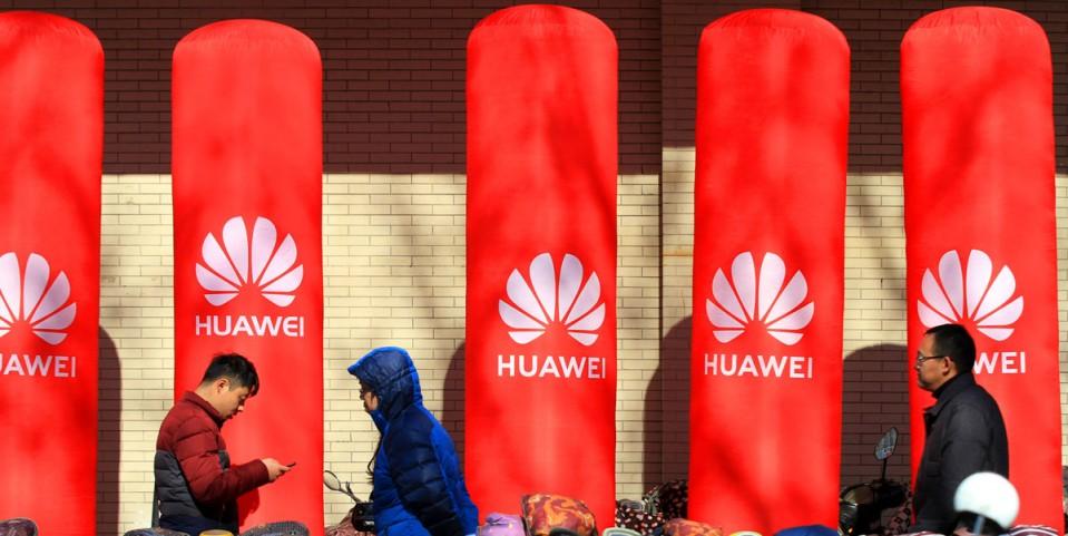 Pedestrians walk past an advertisement for Huawei