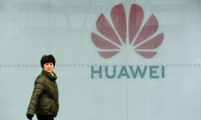 A woman walks in front of Huawei store