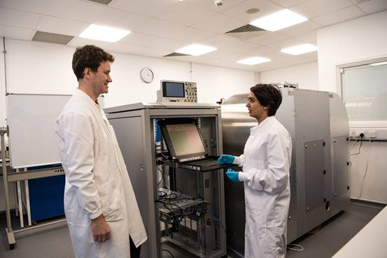 Photo of two researchers standing in front of prototype of DNA data storage machine