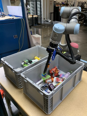 Covariant's robot transferring objects from one gray bin to another