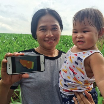 Photo of a farmer in Thailand, holding up an iPhone showing a digital map.