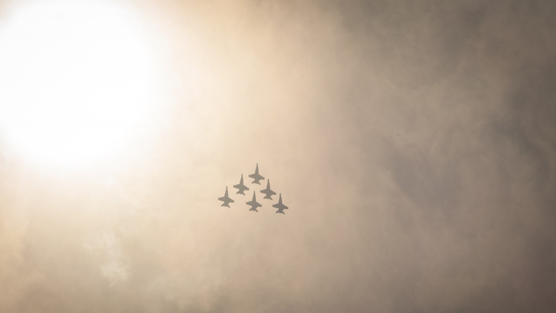 A photo of fighter jets flying in a formation at a distance against a cloudy sky
