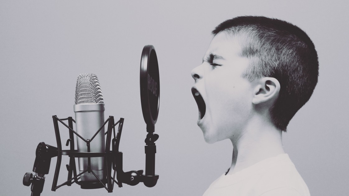 A boy screaming into microphone