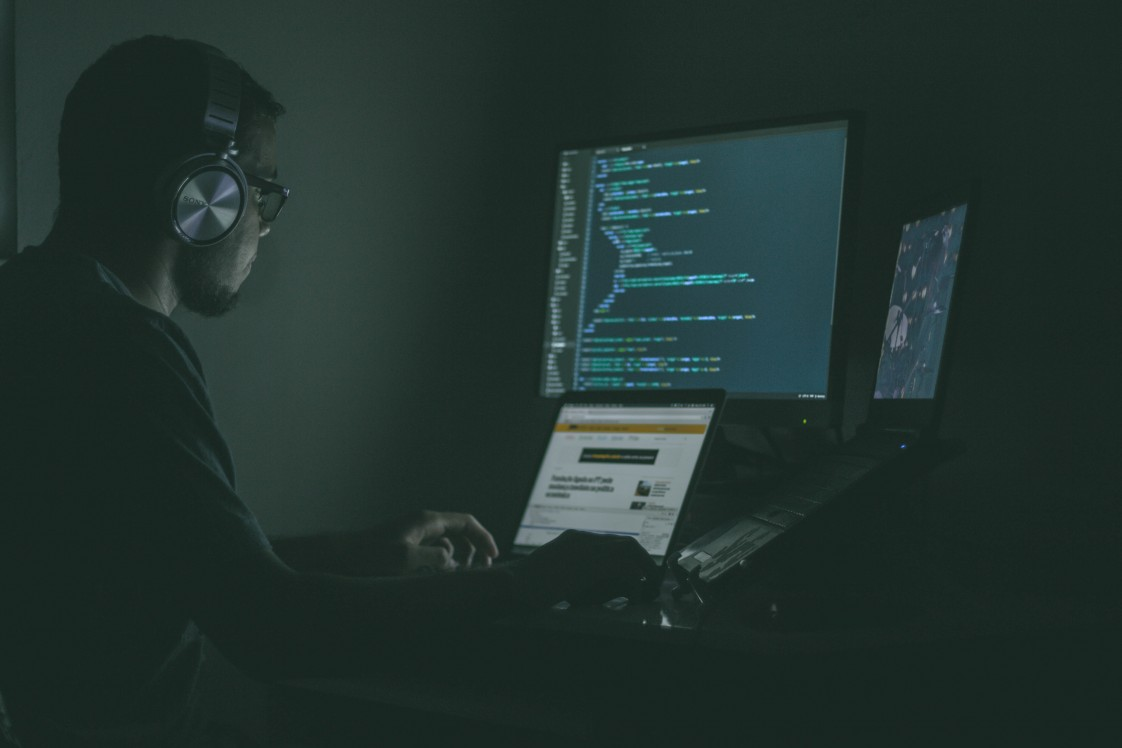 Man sitting at a computer in the dark