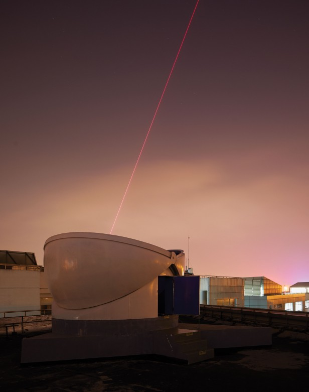 Photograph of receiver at night with a spotting laser visible in the evening sky.