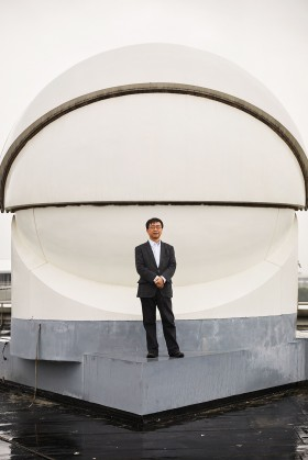 Photograph of Jian-Wei Pan, standing in front of a receiver used in the transmission of ultra-secure signals from the Micius satellite, has helped lead China's quantum efforts. The picture of the receiver on the previous page shows a spotting laser used to help the satellite connect to the ground station.