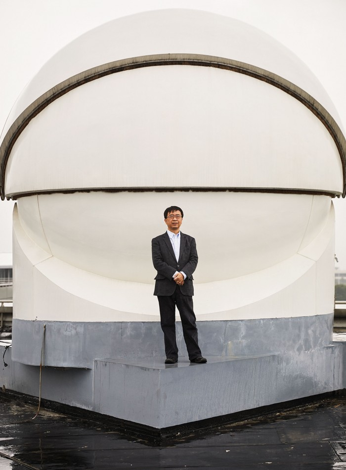 Photograph of Jian-Wei Pan, standing in front of a receiver used in the transmission of ultra-­secure signals from the Micius satellite, has helped lead China's quantum efforts. The picture of the receiver on the previous page shows a spotting laser used to help the satellite connect to the ground station.