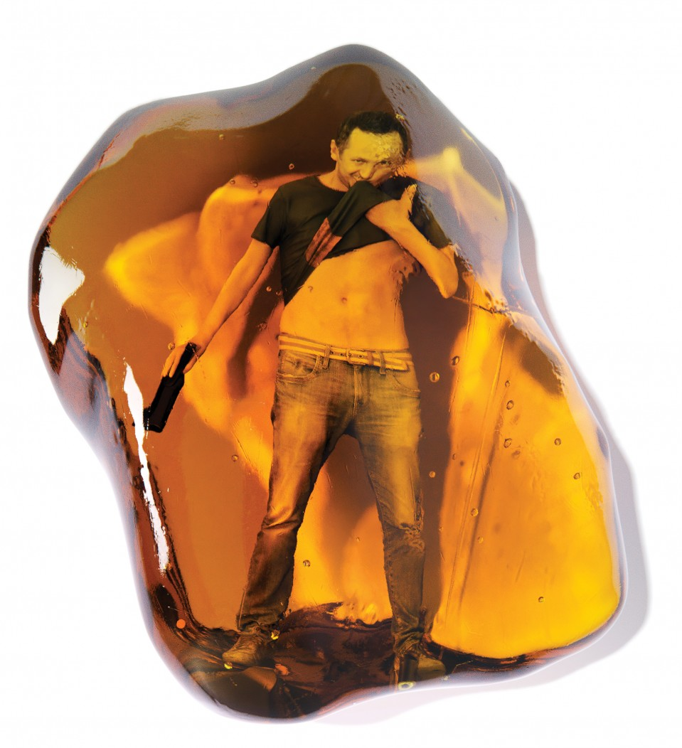 conceptual illustration of a young man drinking a beer, trapped inside a piece of amber