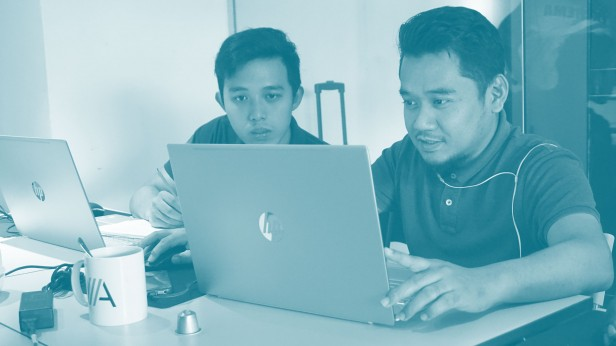 Two remote employees in Kuala Lumpur work on laptops