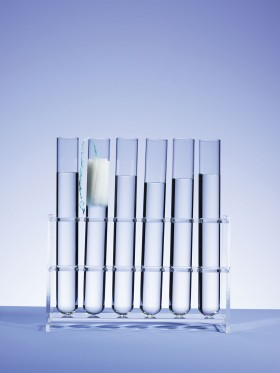 Photo of test tubes, one holding a tampon