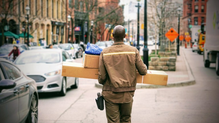 Photo of a delivery man carrying package