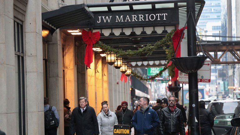 Shoppers walk by a Marriott sign