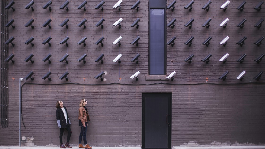 Photo of two women in front of a wall of CCTV cameras