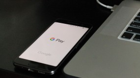 An image of a smartphone with the Google Pay application open on the screen, sitting next to a laptop computer.