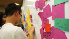 Student at post-it-note-filled whiteboard
