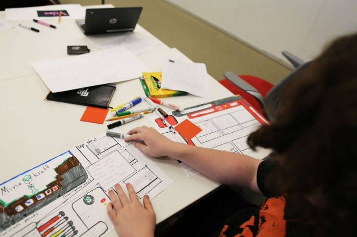Student sits in front of hand-drawn digital interface interface