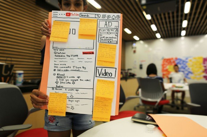 A student holds up a poster design of a hand-drawn YouTube web interface