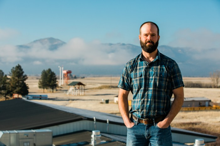 Photo of Jason standing on the roof of the Missoula Fire Lab with smoke jumper equipment behind him.