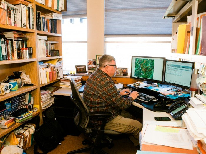 Photograph of Chuck as he works in his office at the Missoula Fire Lab and uses a program that models fire activity and the probability of spread. The program allows scientists to model fire spread and subsequently determine if action needs to be taken or what action they should be thinking about. Or, conversely, no action at all.