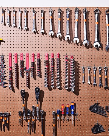 Wrenches and other tools hanging on a pegboard