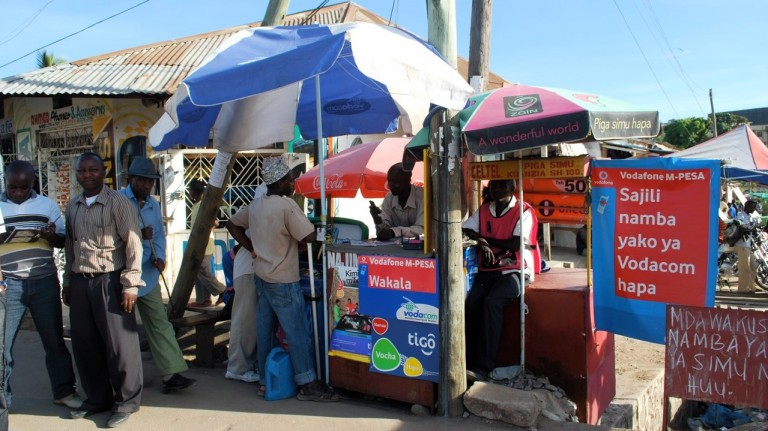 A street vendor in Tanzania with signs showing that they accept Vodafone's M-Pesa digital payment system.