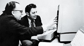 Photo of JCR Licklider and Al Vezza in front of a computer