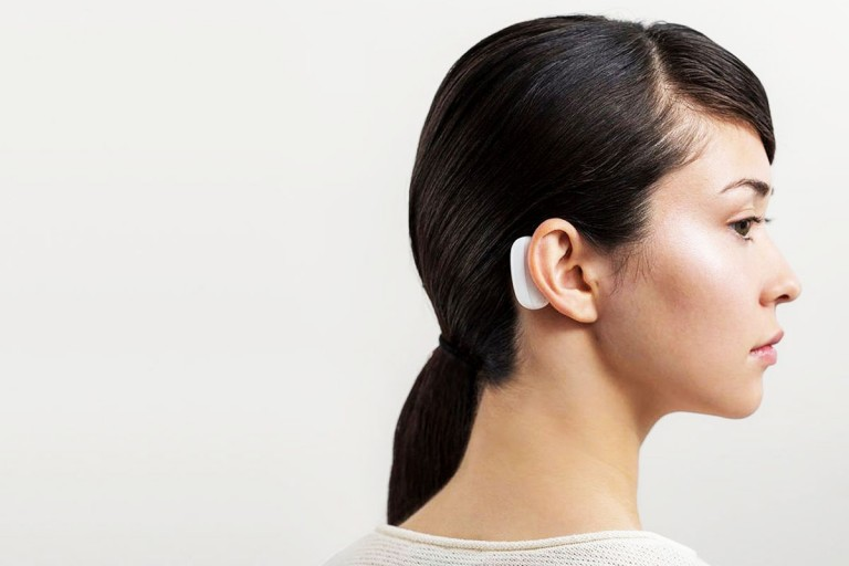 An image of a woman with a device behind her ear