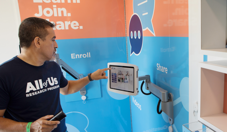 A man interacting with an NIH kiosk part of a traveling exhibit