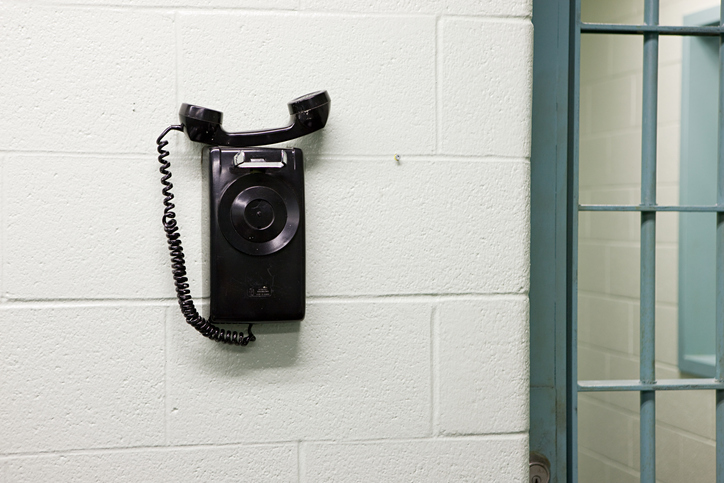 A telephone attached to the wall in a prison