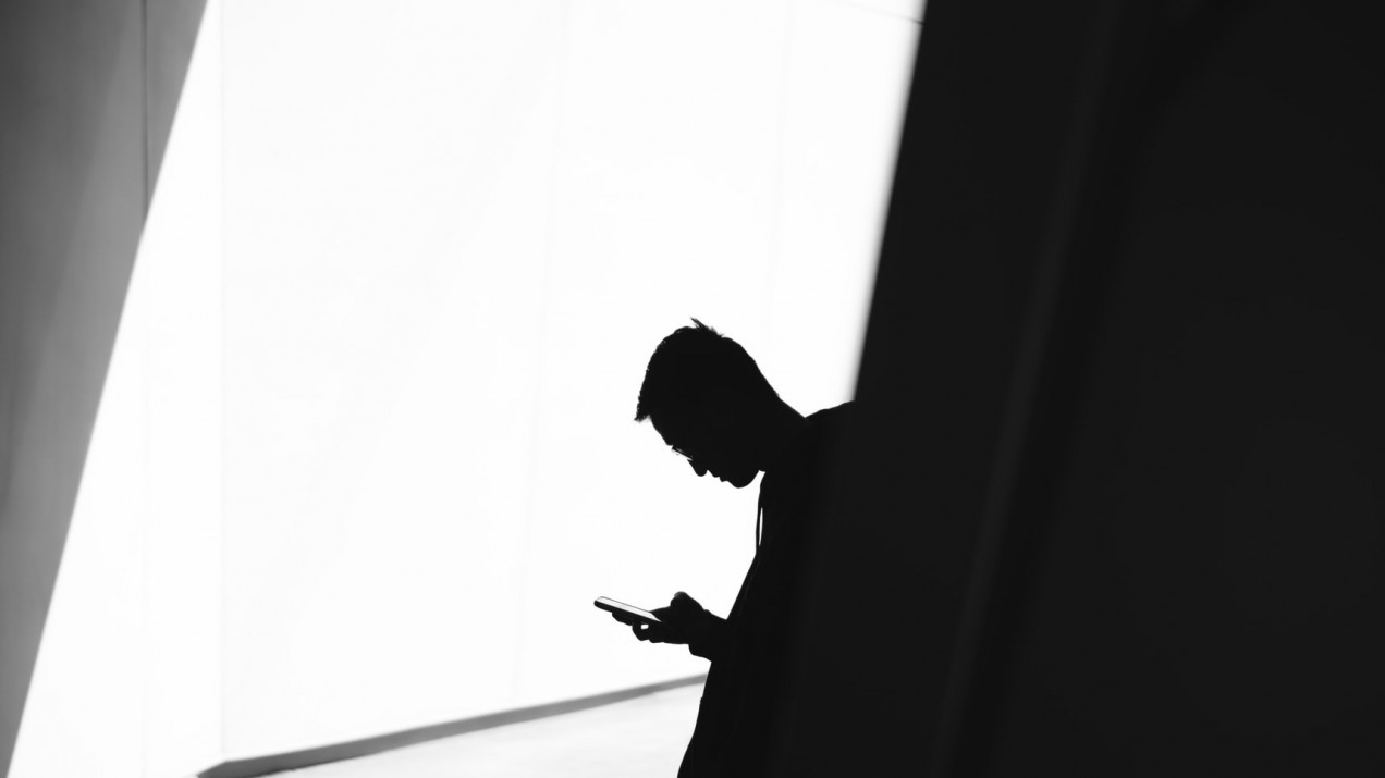 image of boy using phone in shadows black and white